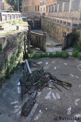 Resti del legno delle porte giacciono sul pavimento della conca come dei rifiuti qualsiasi.